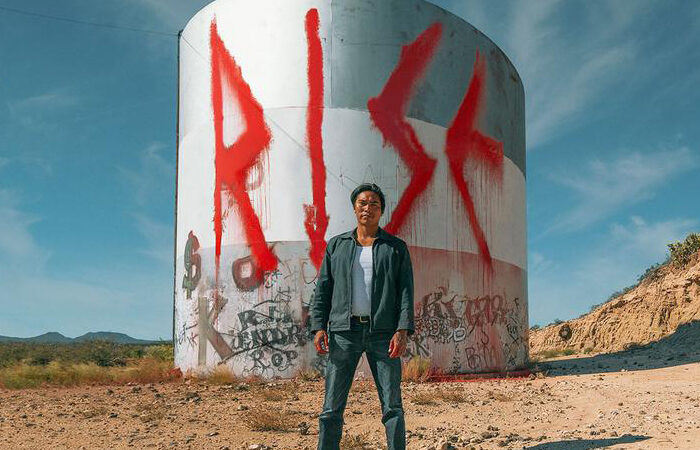 An indigenous man stands in front of large, spray painted letters spelling 'Rise'