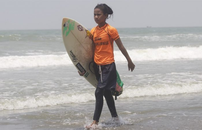 A young girl carries a surfboard in Bangladesh